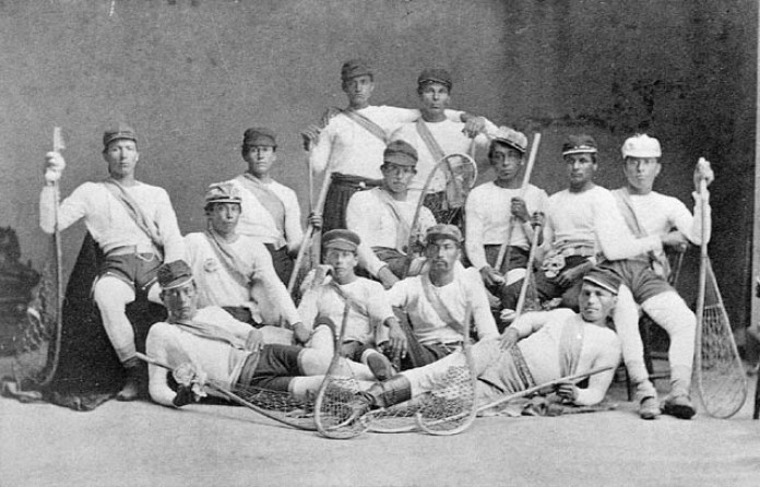 A group of Iroquois men holding traditional lacrosse sticks