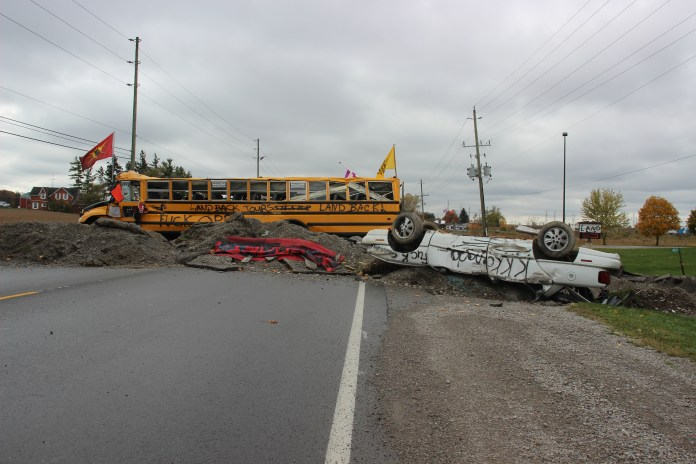 A barricade on the road made up of an abandoned school bus and car.