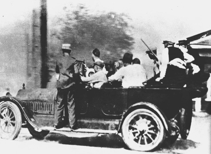 Automobile loaded with men, some holding guns