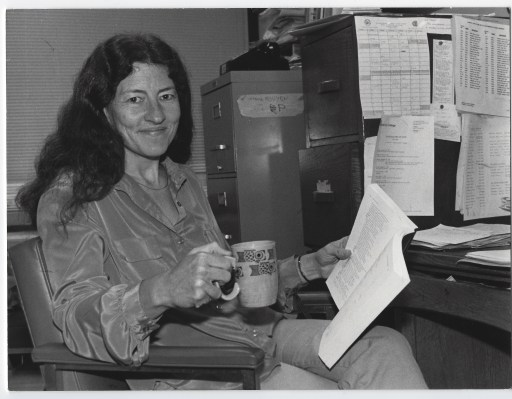 Marty Kendall sitting at her desk in her City College office holding a coffee cup and a book