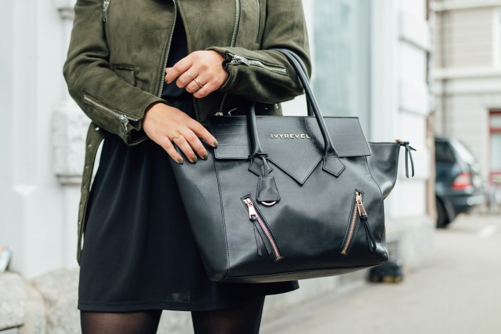 Closeup of black leather bag and little black dress with jacket