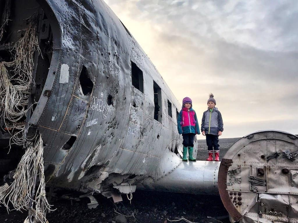 kids standing on Plane Wreck at Sólheimasandur - Iceland in winter