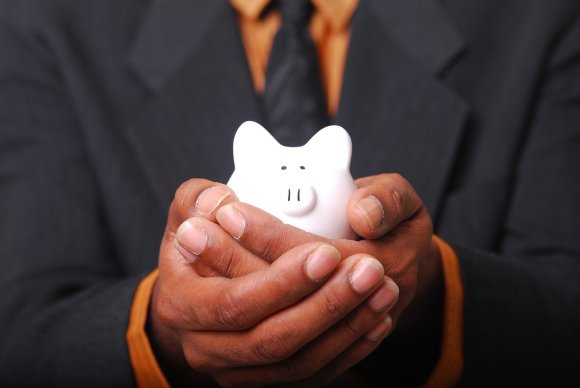 man in suit and tie holding a small piggy bank | terrible at saving money
