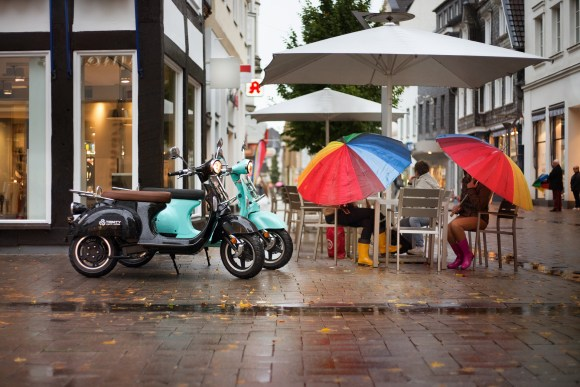 electric scooter and two women with colourful umbrellas sat outside a cafe