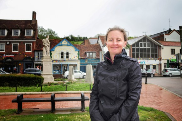 Woman wearing black jacket, smiling in town centre