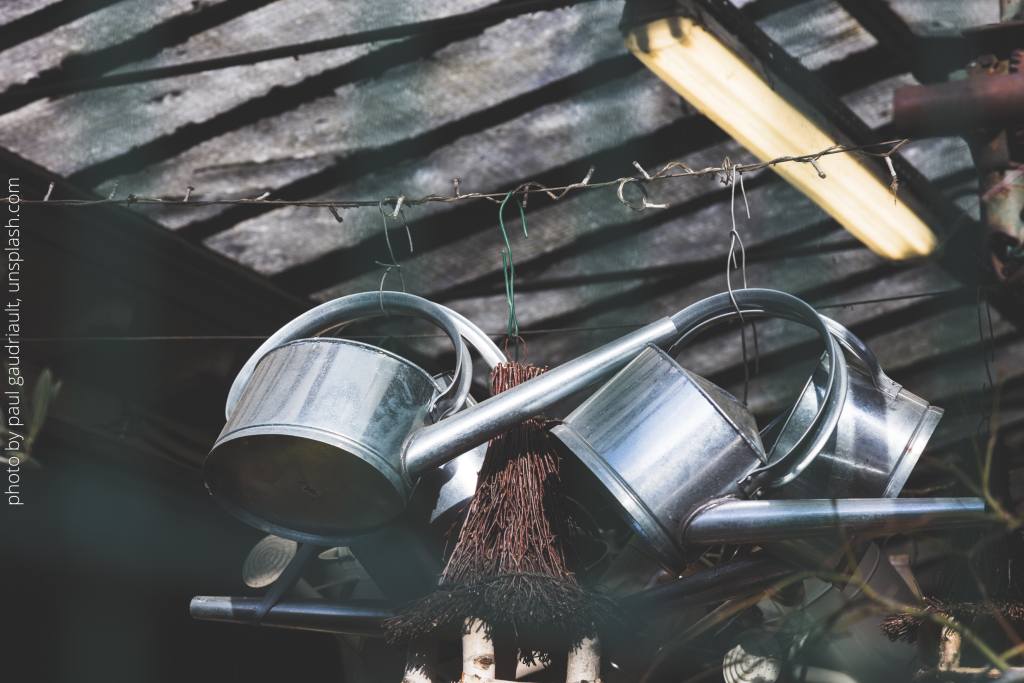 three shiny, unused watering cans hanging on a wire in a shed