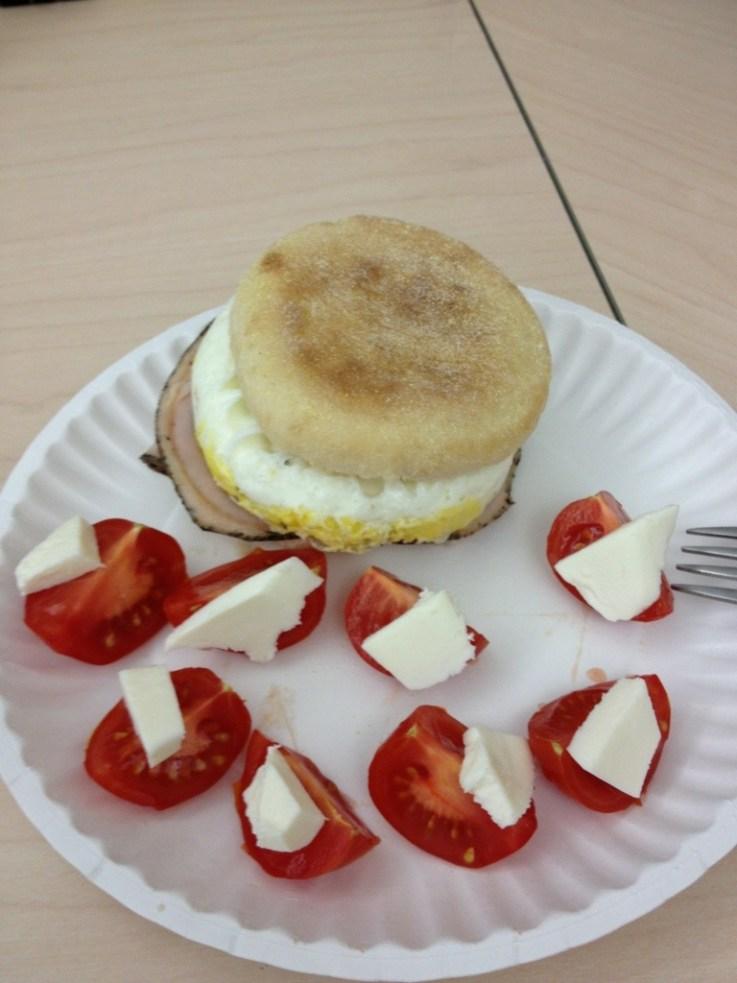 Eggs, chicken breast slices on muffin, tomato and mozarella