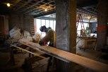 A construction worker sands a wooden plank.