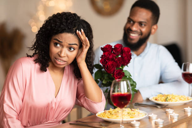Bad First Impression And Blind Date Concept. Dissatisfied shocked black woman rejecting excited emotional obsessed man who giving her flowers, young couple sitting at table in cafe
