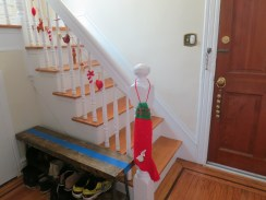 The felted garland on the staircase and sleigh bells on the door are new purchases from Etsy; the knit stocking is from childhood.