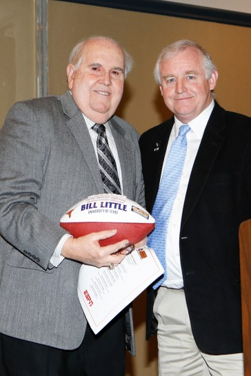 Former Texas SID Bill Little receives a commemorative football from FWAA President Kirk Bohls. Photo by Melissa Macatee.