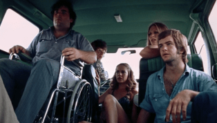 The group of five looks at the Hitchhiker in horror