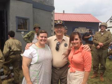 An original 94th soldier poses with two of the female reenactors of the unit. Credit: Brian Schade.