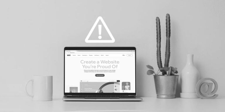 Wix.com (not recommended) pulled up on laptop screen next to mug, cactus, vase, and @ symbol sign