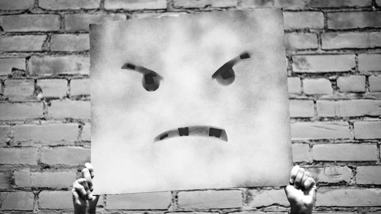 Hands holding up an angry face painted on a square canvas