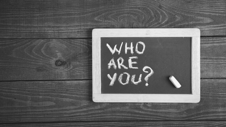 "The words ""who are you?"" written on a small chalkboard"