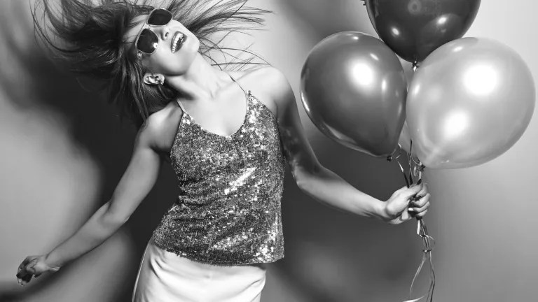Woman holds balloons while smiling and flipping her hair in sequined dress