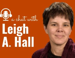 """Graphic that reads """"A Chat with Leigh A. Hall,"""" with a photo of Leigh smiling and wearing a maroon sweater"""