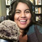 Photo of Jennifer van Alstyne wearing headphones with a microphone smiling