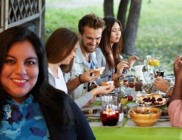 Jennifer van Alstyne standing in front of a table with 4 people and an outdoor holiday feast