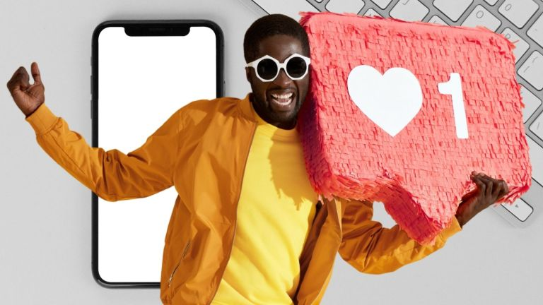 Man with sunglasses smiles and holds a paper mache Instagram heart button, background of graphic is a blank mobile phone screen and a wireless keyboard
