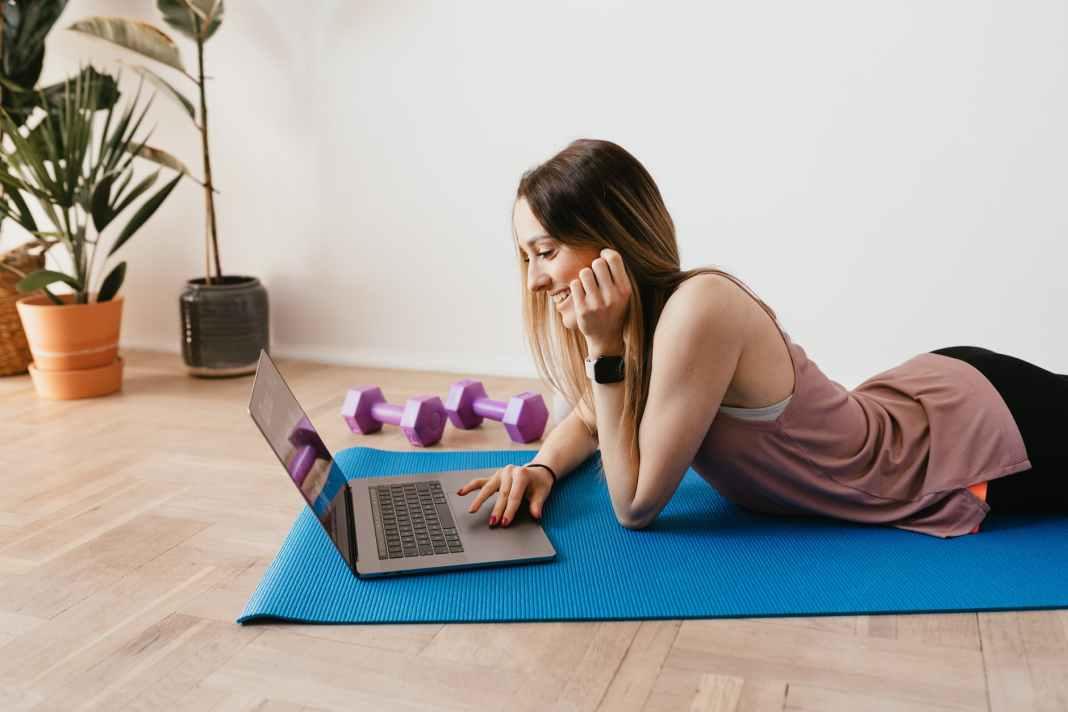 slim woman browsing laptop on yoga mat