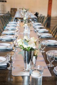Table with table runner, small flower vases, white flowers