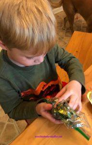 Little boy covering an Easter Egg in glitter.