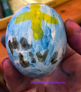 "Blue Easter Egg with Yellow Cross and black words ""He Lives."""