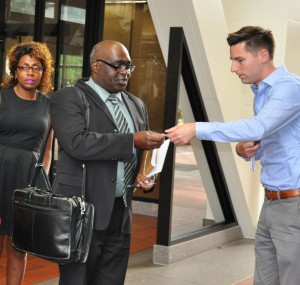 Antoinette Wilson looks on as Karluah's lawyer, Marcus Jarvis receives card from TV reporter.