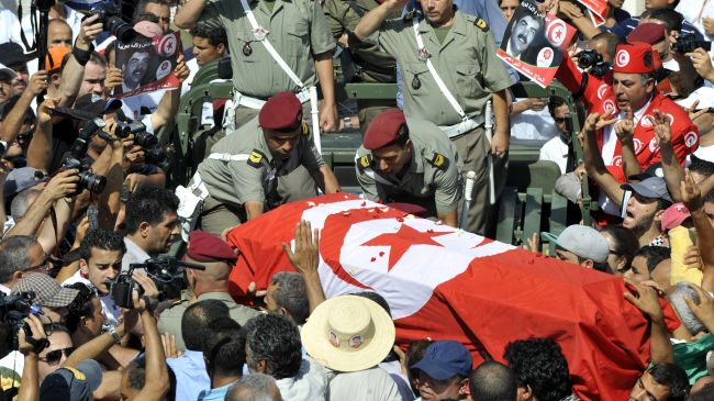 Tunisian soldiers salute as they load the coffin of assassinated opposition leader Mohamed Brahmi during his funeral procession in Tunis on July 27.