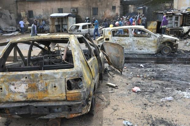 People walk past destroyed cars in Conakry on October 9, 2015, after at least two people were killed and scores hurt in clashes between rival political parties ahead of Guinea's presidential election Cellou Binani, AFP Read more: http://www.digitaljournal.com/news/world/tension-flares-in-guinea-ahead-of-presidential-poll