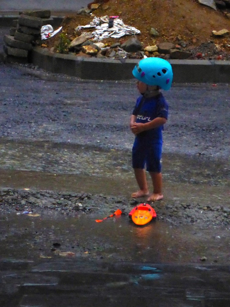 Our river guide - just kidding! This was the owner's son playing in front of the shop. So cute with this rafting helmet and mini-kayak