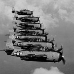 Seven Grumman TBM-3D Avenger bombers of night torpedo squadron VT(N)-90 flying in formation in January 1945. The squadron was part of Night Air Group 90 on the carrier USS Enterprise (CV-6). Note radar pods in right-side wings, and the distinctive tail insignia.