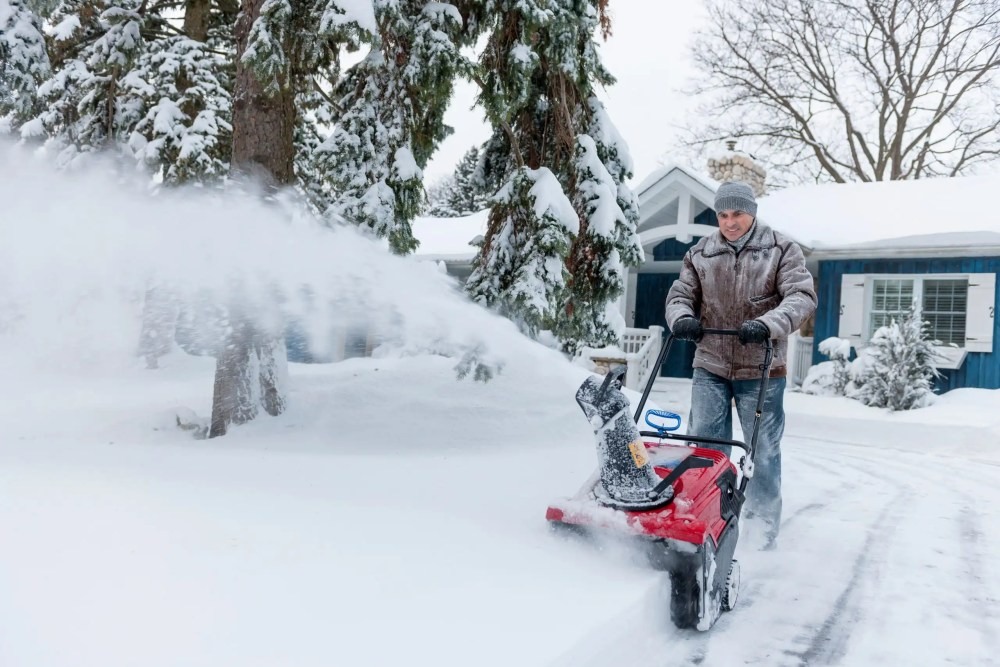 Man clearing driveway with battery powered snow blower