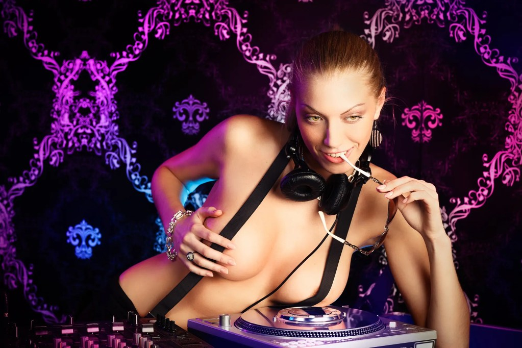 Sexy young blonde lady DJ in suspenders at night club