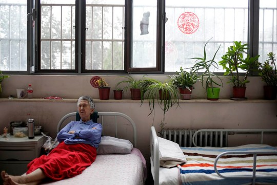 A woman rests in bed at the Songtang Hospice, Beijing, July 19, 2016. The plants by the window were donated by hospice volunteers.