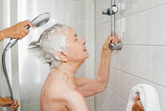 Chiara Micheletti helps her mother Marisa Vesco take a shower in Cossato, Italy, June 7, 2015.