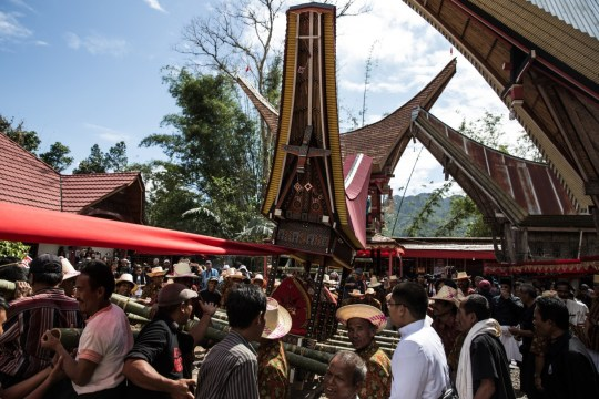 Villagers and relatives gather as they prepare for a parade during the Rambu Solo of V.T. Sarangullo in La'Bo village, Toraja, South Sulawesi, Indonesia. After the animals are killed, a feast is thrown and the body of the deceased placed in a stone grave, or Liang.