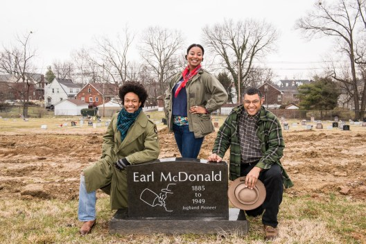 Brian Farrow, Vania Marie Kinard and Dom Flemons pose beside Earl McDonald's grave. Dom Flemons, a founding member of the Piedmont string-band ensemble the Carolina Chocolate Drops, visits Louisville Cemetery, burial site of Earl McDonald and Sara Martin Friday, March 4, 2016 in Louisville, Ky. (Photo by Brian Bohannon)