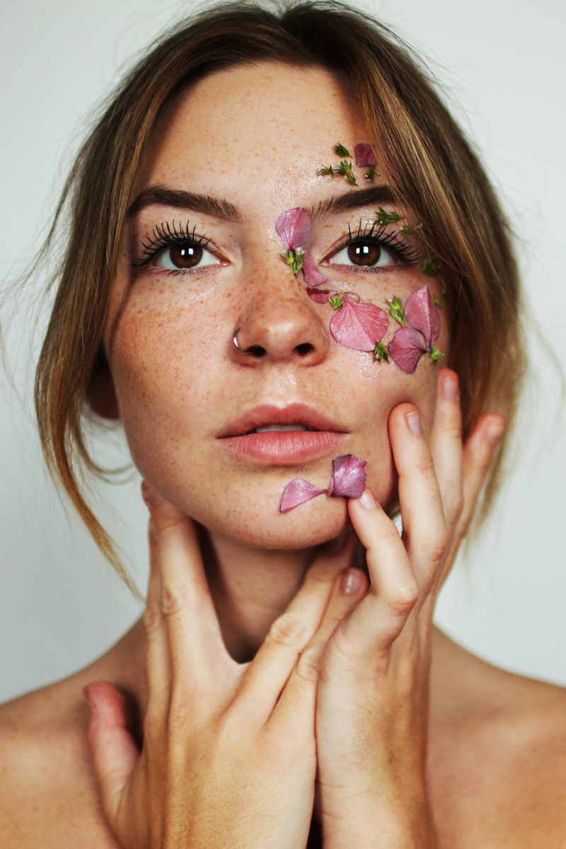 beauty women, with petals on face and hand cupping her cheek and chin