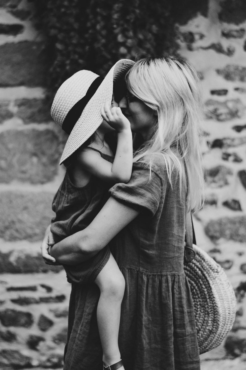 black and white image, of a mum with a toddler. The toddler is a girl and in the arms of her mum with a large hat on