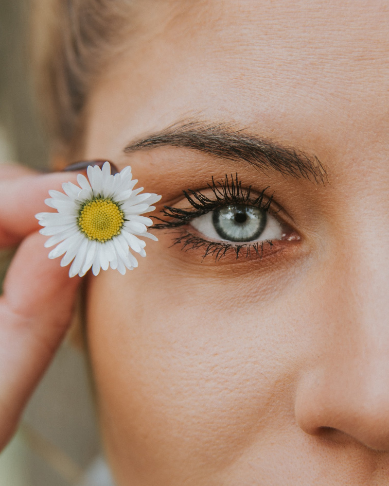 women face, holding flower next to eye... self care