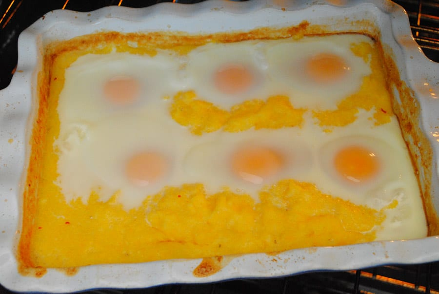 Eggs cracked on top in the Polenta Breakfast Bake