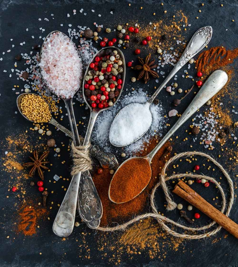 Whole and ground spices on spoons