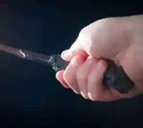 Child hand with magic wand on black contrast background with flash light