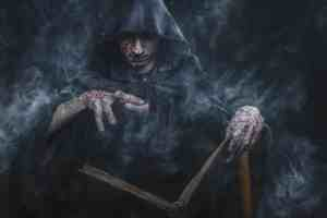 Dark necromancer, sorcerer casting black magic from his spell book, the book of shadows