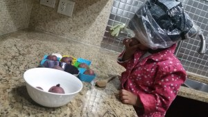 Asha playing with potatoes and bag in kitchen