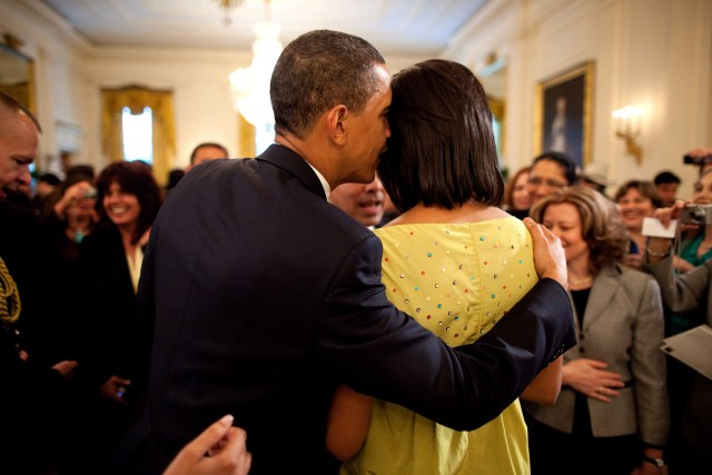 President Barack Obama whispers into First Lady Michelle ObamaÕs ear during the White House Cinco de Mayo celebration May 4, 2009. Official White House Photo by Pete Souza. This official White House photograph is being made available for publication by news organizations and/or for personal use printing by the subject(s) of the photograph. The photograph may not be manipulated in any way or used in materials, advertisements, products, or promotions that in any way suggest approval or endorsement of the President, the First Family, or the White House.