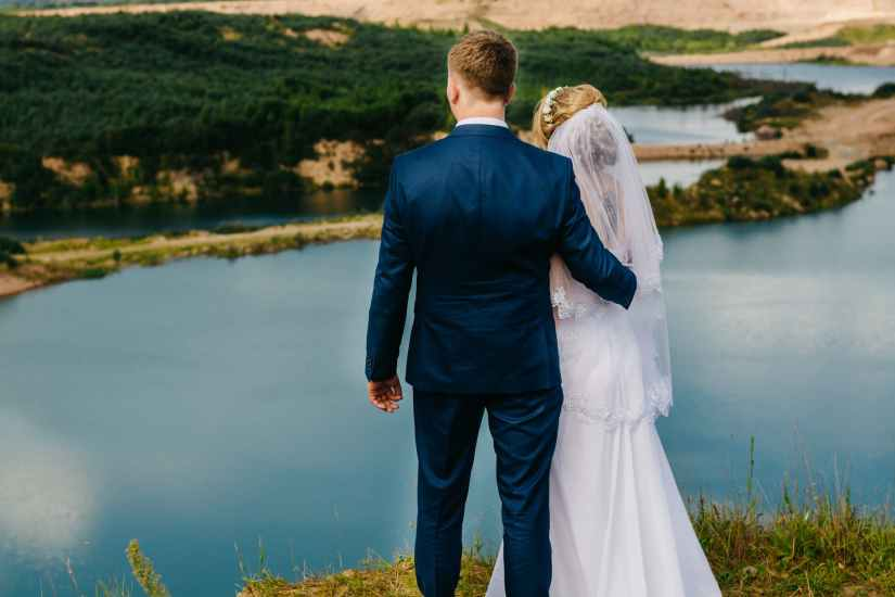 couple standing near body of water